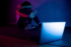 有计算机膝上型计算机在网上被滥用的痛苦cyberbullying和骚扰的哀伤和害怕的女性少年  库存图片