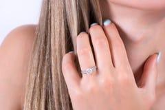 有订婚婚戒的年轻女性举行在头发的手在手指和手 免版税库存图片