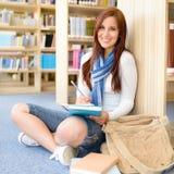 有记事本的高中图书馆微笑的学员 免版税库存照片