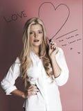 有记号笔图画心脏的白肤金发的妇女 库存图片