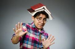 有许多书的滑稽的学生 免版税库存照片