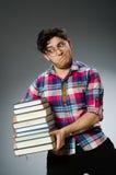 有许多书的滑稽的学生 免版税库存图片