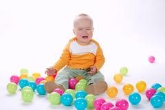 有许多五颜六色的球的逗人喜爱的哭泣的女孩 库存照片
