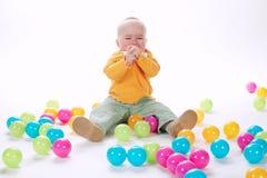 有许多五颜六色的球的逗人喜爱的哭泣的女孩 库存图片