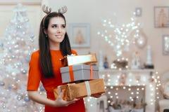 有许多圣诞节礼物的快乐的妇女在装饰的家 免版税库存照片