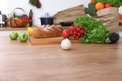 有许多新鲜蔬菜和果子的书桌在厨房里 烹调,素食主义者和购物的概念 免版税库存照片