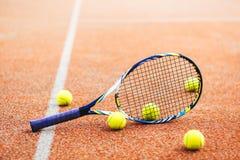有许多球的网球拍在红土网球场 免版税库存图片