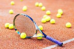 有许多球黏土法院的网球拍 免版税库存图片