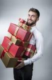 有许多礼物箱子的可爱的人在他的胳膊 图库摄影