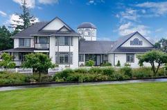有许多窗口、白色尖桩篱栅和庭院区域的大白色房子 免版税库存图片