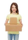 有许多纸板箱的微笑的小女孩 免版税库存照片
