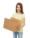 有许多纸板箱的微笑的小女孩 免版税库存图片