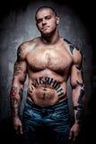 有许多纹身花刺的肌肉年轻人 免版税库存图片