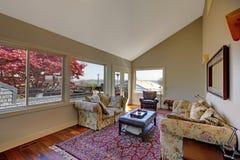 有许多视窗和红色地毯的客厅。 免版税库存图片