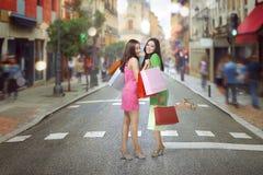 有许多购物袋的美丽的两个亚洲人妇女 免版税库存图片
