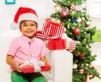 有许多xmas礼物的愉快的小男孩 库存照片