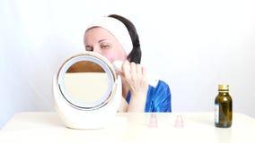 有设备的一个女孩执行面孔的皮肤的microdermabrasion在白色背景的,坐与镜子 股票视频