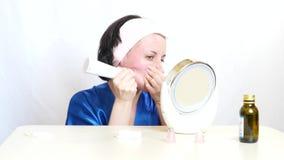 有设备的一个女孩执行面孔的皮肤的microdermabrasion在白色背景的 秀丽的概念和 股票视频