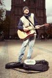 有设法的吉他的叫化子挣在公众的钱 免版税库存照片