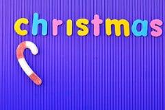 有词圣诞节的一个红色和白色镶边棒棒糖 免版税图库摄影