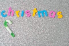 有词圣诞节的一个绿色和白色镶边棒棒糖 库存照片