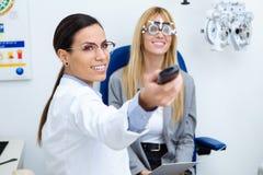 有试验框架的妇女验光师检查患者的视觉的在眼科 在医生的选择聚焦 免版税库存照片