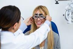 有试验框架的妇女验光师检查患者的视觉的在眼科 免版税库存图片