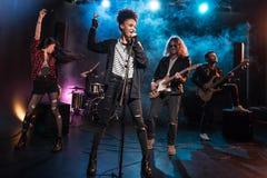有话筒的女歌手和执行硬岩音乐的摇滚乐队 图库摄影