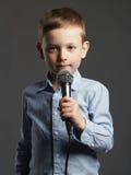 有话筒的小男孩 唱歌在卡拉OK演唱的孩子 库存照片