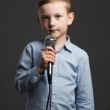 有话筒的小男孩 唱歌在卡拉OK演唱的孩子 免版税库存照片