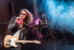 有话筒的男性歌手和执行硬岩音乐的摇滚乐队 免版税库存照片