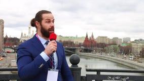 有话筒的男性记者告诉在城市的背景的新闻照相机 俄罗斯,莫斯科 影视素材