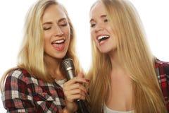 有话筒的获得两个秀丽的女孩唱和乐趣 库存图片