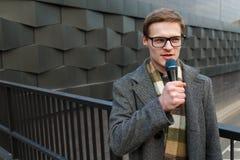 有话筒的年轻新闻记者在街道上播放 时尚或商业新闻 免版税图库摄影