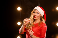 有话筒的年轻白肤金发的可爱的在阶段的妇女和闪烁发光物 免版税库存图片