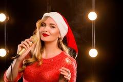 有话筒的年轻白肤金发的可爱的在阶段的妇女和闪烁发光物 免版税图库摄影