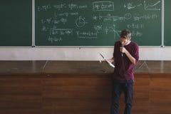 有话筒讲的和教的学生的年轻教授讲师在大教室里 库存照片