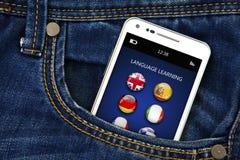 有语言学习应用的手机在牛仔裤装在口袋里 免版税库存照片