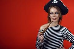 有诱惑拿着一只木被雕刻的烟斗的构成佩带的海盗服装和竖起的帽子的华美的妇女 免版税库存照片