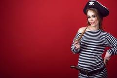 有诱惑拿着一只木被雕刻的烟斗的构成佩带的海盗服装和竖起的帽子的华美的妇女 库存图片