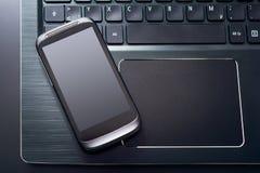 有说谎在一个黑笔记本的键盘的左边缘的反射的黑手机,顶视图 库存图片