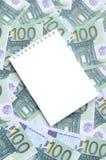 有说谎在一套的干净的页的白色笔记本绿色金钱 免版税库存图片