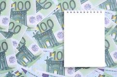有说谎在一套的干净的页的白色笔记本绿色金钱 图库摄影