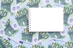 有说谎在一套的干净的页的白色笔记本绿色金钱 免版税图库摄影