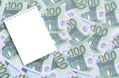 有说谎在一套的干净的页的白色笔记本绿色金钱 库存图片