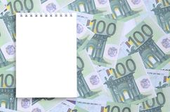 有说谎在一套的干净的页的白色笔记本绿色金钱 免版税库存照片