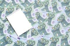 有说谎在一套的干净的页的白色笔记本绿色金钱 库存照片