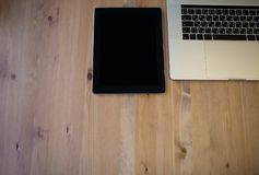 有说谎在一张木桌上的空白的拷贝空间屏幕的现代数字式片剂在便携式的便携式计算机附近 库存照片