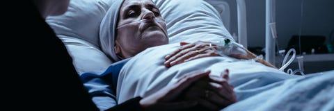 有说谎在医院病床上的一根呼吸管的死的妇女举行了b 免版税库存照片