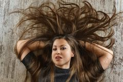 有说谎在地板上的俏丽的发型的年轻女人 r 免版税库存图片